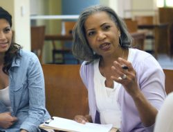 African American female mental health professional talks with the members of a support group.
