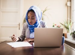 Muslim businesswoman working at home due to pandemic isolation. She is wearing blue hijab. Belgrade, Serbia